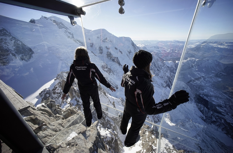 Employees stand in the 'Step into the Void' installation at the Aiguille du Midi mountain peak above Chamonix, in the French Alps