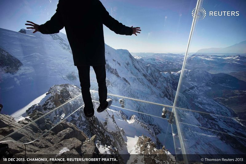 A journalist, wearing slippers to protect the glass floor, stands in the 'Step into the Void' installation during a press visit at the Aiguille du Midi mountain peak above Chamonix, in the French Alps